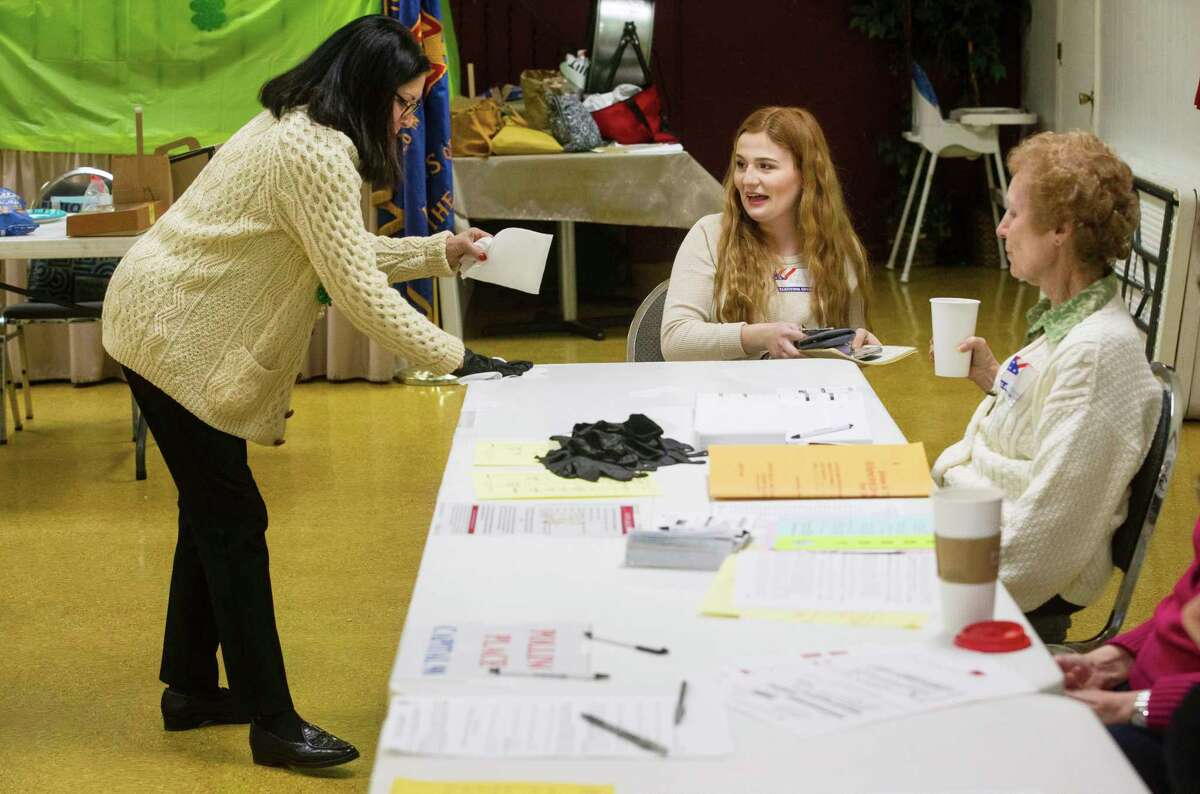 Eva Griffin recoils as Carol Kitterman uses disinfectant wipes to clean off the voter check-in table during the primary election at the Veterans of Foreign Wars Post 755 on Old Jacksonville Road in Springfield, Ill., Tuesday, March 17, 2020. (Ted Schurter/The State Journal-Register via AP)