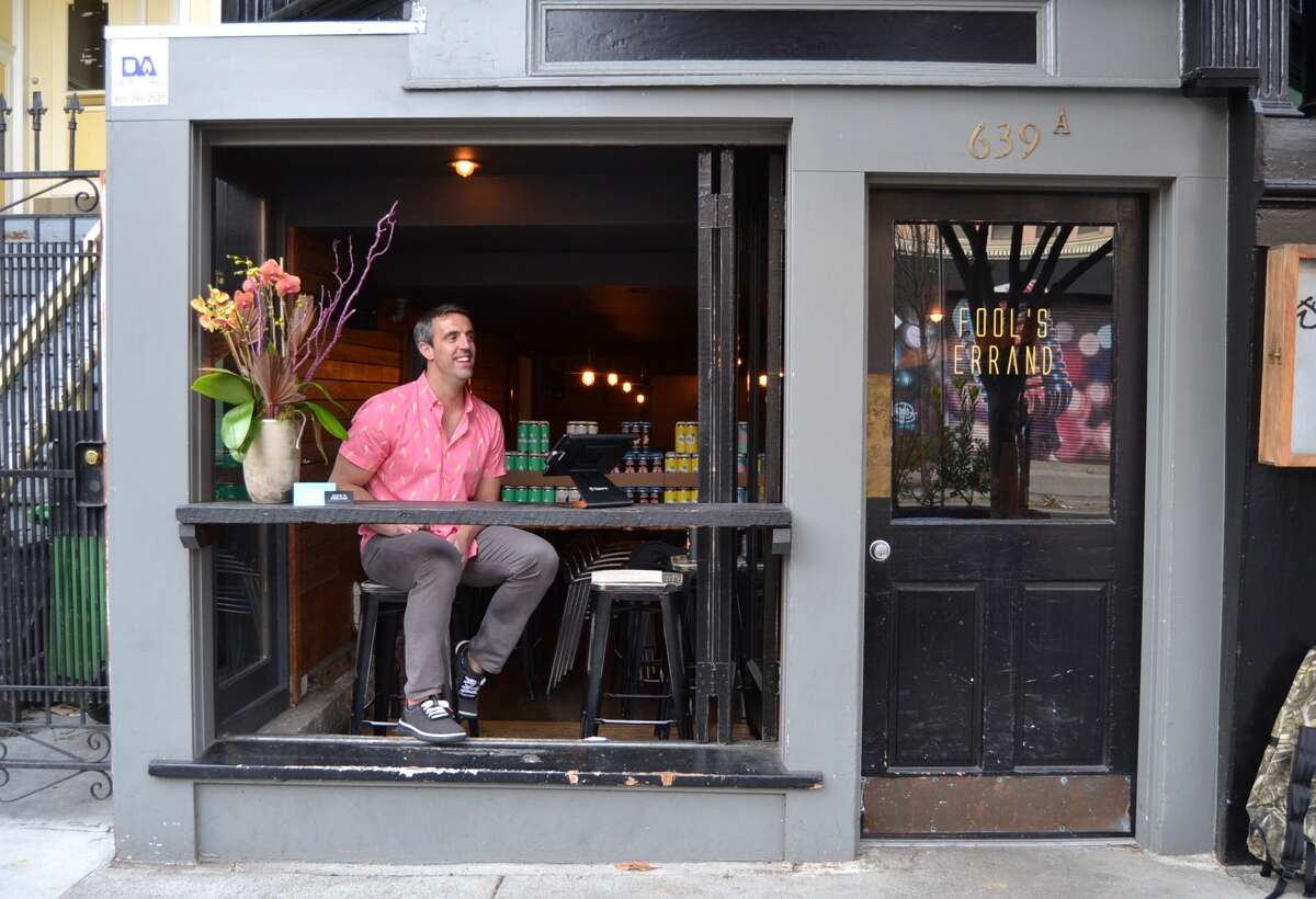 John Dampeer sits in the window of his Divisadero Street beer and wine bar, Fool's Errand during the shelter-in-place shutdown in San Francisco on March 17, 2020.