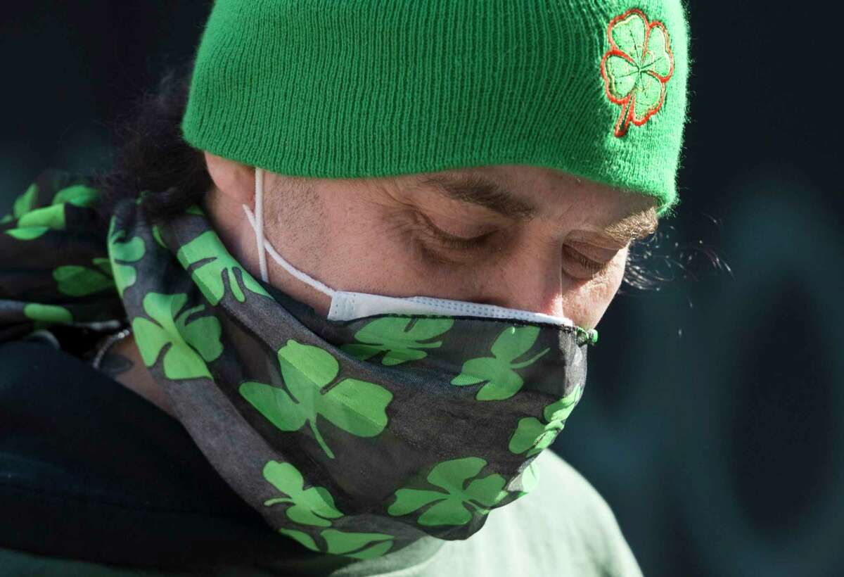A man wears a mask and a hat with an Irish symbol of shamrock designs as he walks in downtown Vancouver, British Columbia, Tuesday, March 17, 2020. (Jonathan Hayward/The Canadian Press via AP)