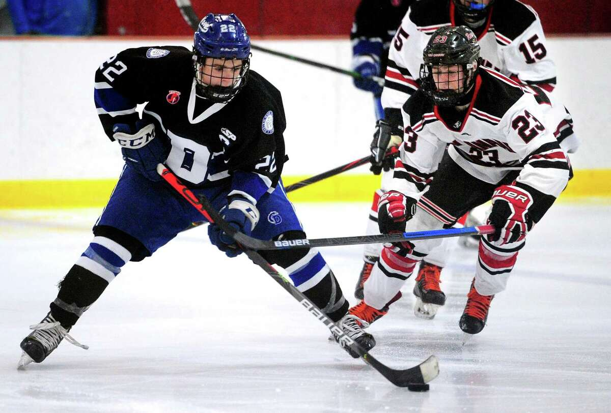 Darien's Bennett McDermott (22) manuevers the puck as New Canaan's Boden Gammill (23) looks to disrupt during FCIAC boys hockey championship action on March 7.