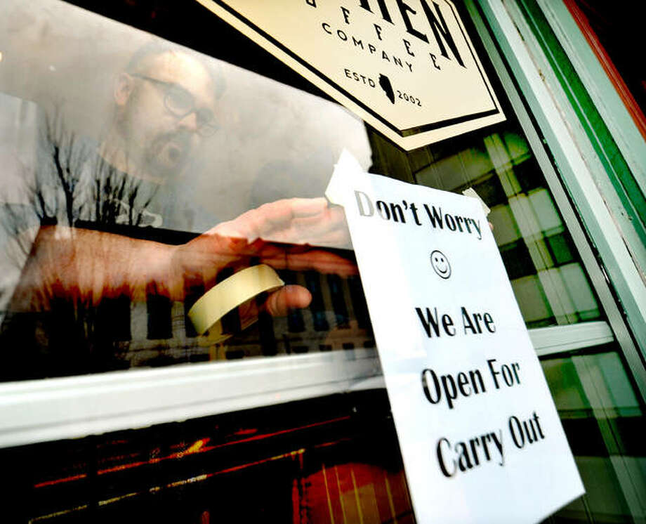 Trevor Taynor of 222 Artisan Bakery and Cafe hangs a sign on the front door Monday letting customers know that even though the dining room will be closed due to the coronavirus the store will still be open for takeout.