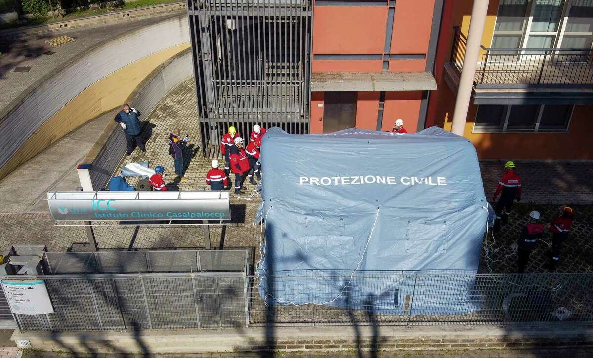 Italian Civil Protection personnel set up a tent for the arrival of COVID-19 patients outside the Istituto Clinico Casalpalocco Covid 3 hospital, which has set up 12 ICU positions, in Casalpalocco, on the outskirts of Rome, Wednesday, March 18, 2020. For most people, the new coronavirus causes only mild or moderate symptoms. For some it can cause more severe illness, especially in older adults and people with existing health problems.