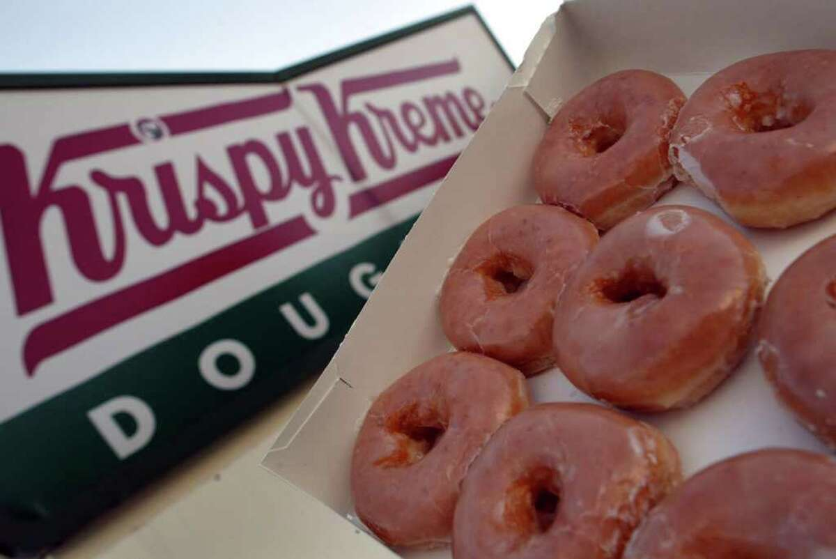 Glazed Krispy Kreme doughnuts are seen May 17, 2004 in Miami, Florida. Krispy Kreme All customers can get a free coffee, no purchase needed.Rewards members get a free donut to-go with the free cup of joe. Godiva Customers can get 30 percent off coffee bags at Godiva Boutiques and online.