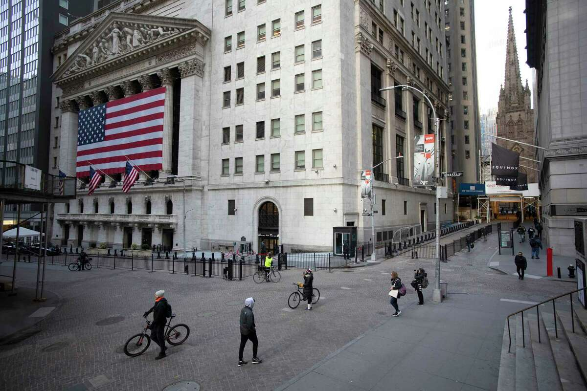 A few people walk on Wall Street in front of the New York Stock Exchange on Wednesday.