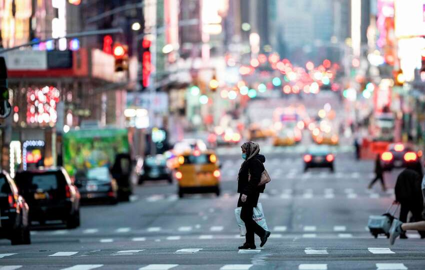 A woman wearing a mask crosses the street in Times Square in Manhattan on March 17, 2020 in New York City. - The coronavirus outbreak has transformed the US virtually overnight from a place of boundless consumerism to one suddenly constrained by nesting and social distancing. (Photo by Johannes EISELE / AFP)