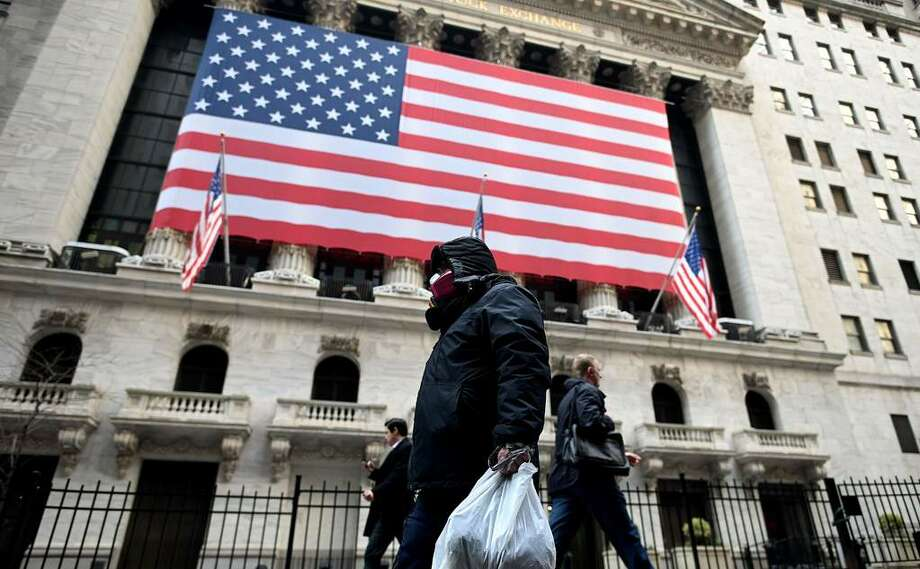 A man wearing a mask walks by the New York Stock Exchange (NYSE) on March 17, 2020 at Wall Street in New York City. - Wall Street stocks rallied Tuesday on expectations for massive federal stimulus to address the economic hit from the coronavirus, partially recovering some of their losses from the prior session. (Photo by Johannes EISELE / AFP) Photo: JOHANNES EISELE, Getty / AFP or licensors