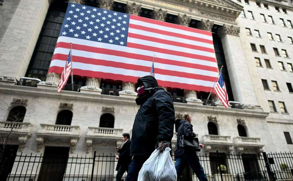 A man wearing a mask walks by the New York Stock Exchange (NYSE) on March 17, 2020 at Wall Street in New York City. - Wall Street stocks rallied Tuesday on expectations for massive federal stimulus to address the economic hit from the coronavirus, partially recovering some of their losses from the prior session. (Photo by Johannes EISELE / AFP)