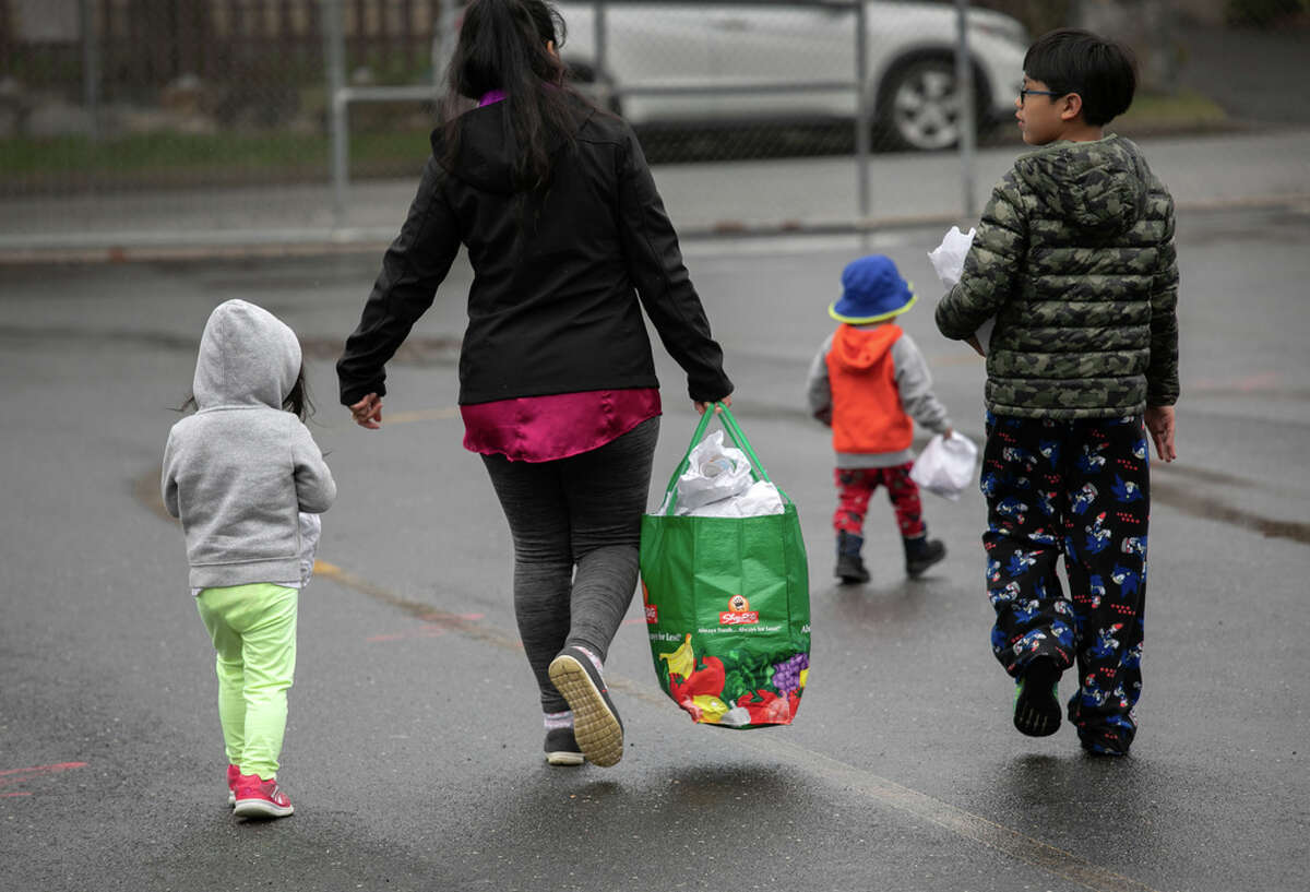 FILE. A family carries home bagged meals given out as part of a Connecticut schools' meals program.