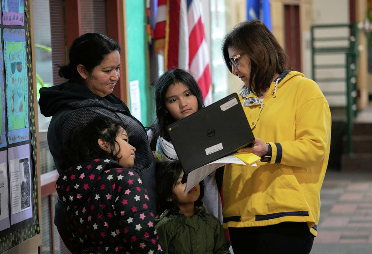 Bilingual teacher Maria Sanislo (R) explains a Google Chromebook to a family at KT Murphy Elementary School on March 17, 2020 in Stamford, Connecticut. Stamford Public Schools closed last week to help slow the spread of COVID-19, and students are now