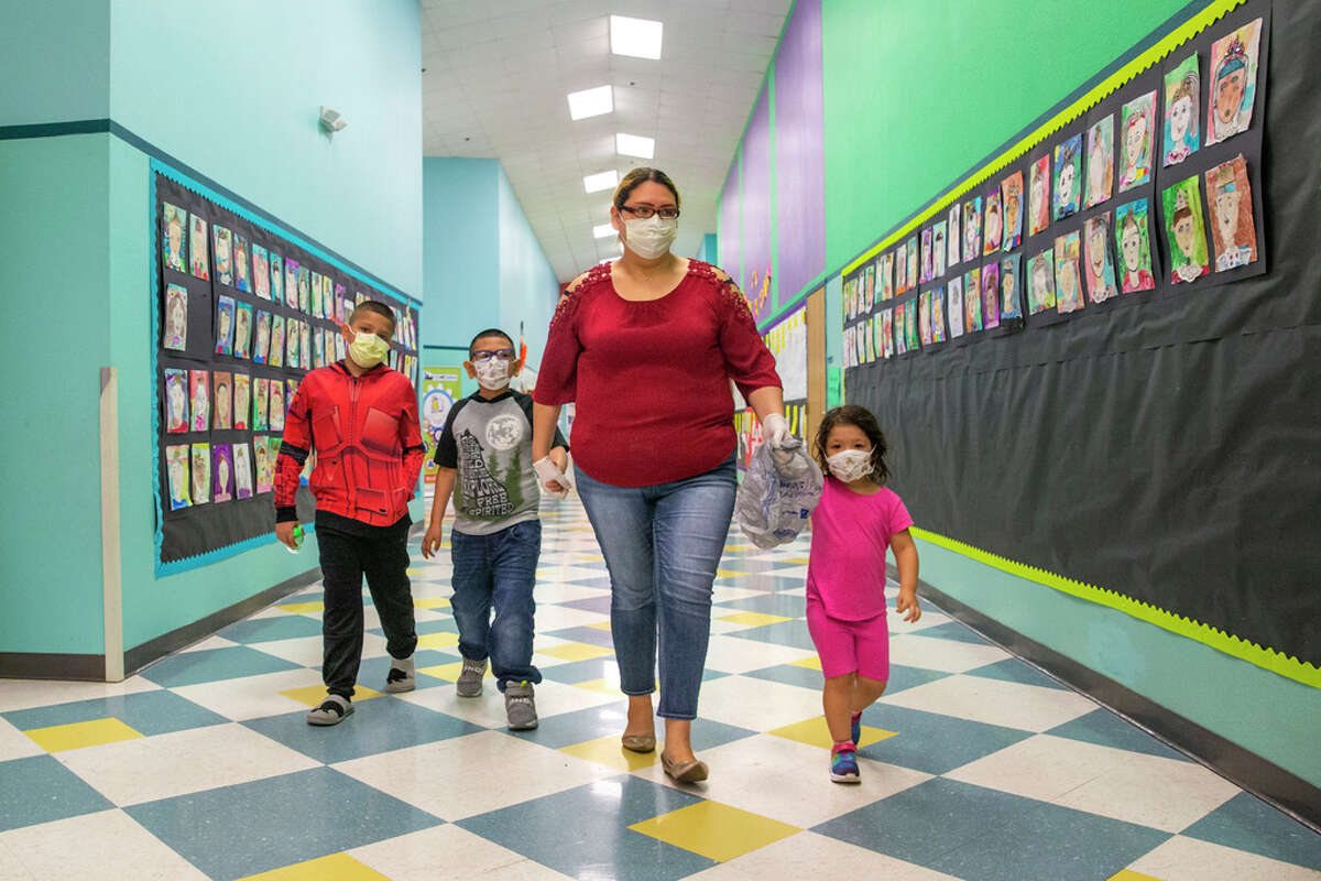 Angie Andrade and her children, from left, Angel, 10, Austin, 7, and Abigail, 3, wear face masks as they walk to pick up free sack lunches at J.T. Saldivar Elementary School in Dallas on Tuesday, March 17, 2020.