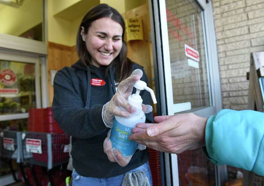 Trader Joe's employee Sophia Therodorou dispenses hand sanitizer to customers as they enter Trader Joe's on Wednesday, March 18, 2020 in Colonie, N.Y. The store was letting 50 people in at a time. (Lori Van Buren/Times Union)