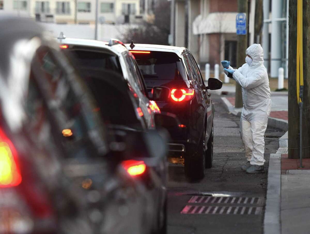 Fernando Ramirez talks with people being tested at the Murphy Medical Associates drive-thru screening for the coronavirus on a private lot in Stamford, Conn. Wednesday, March 18, 2020. Murphy Medical Associates has been offering drive-thru testing for the coronavirus at locations in Greenwich, Stamford, Darien, New Canaan, and Stratford. An appointment must be approved and booked in advance to be tested.