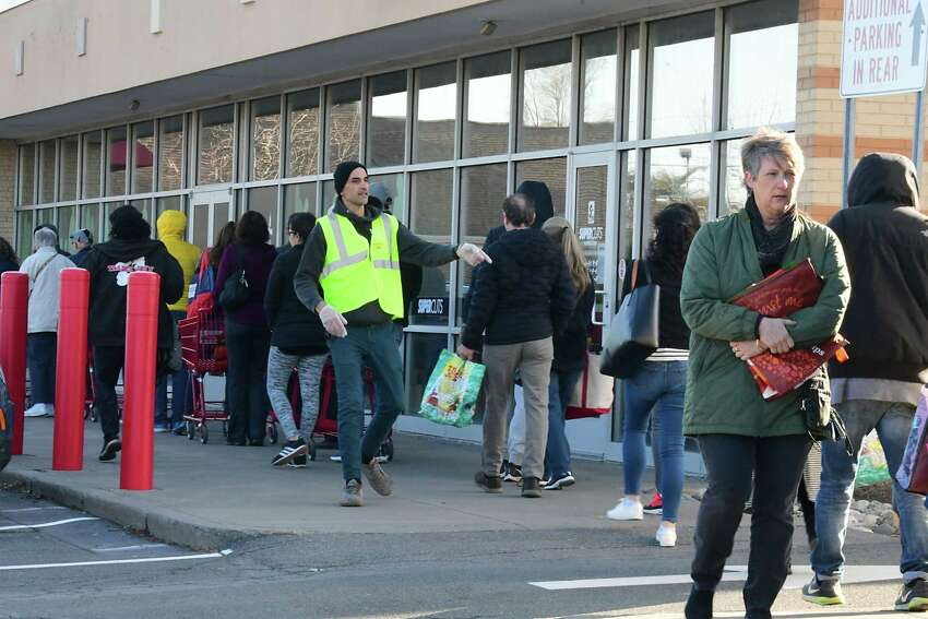 Trader Joe's employee Erman Mercan, center, counts the first 50 people in line as customers line up outside of Trader Joe's before they open for the day at 9:00A.M. on Wednesday, March 18, 2020 in Colonie, N.Y. The store was letting 50 people in at a time. (Lori Van Buren/Times Union)