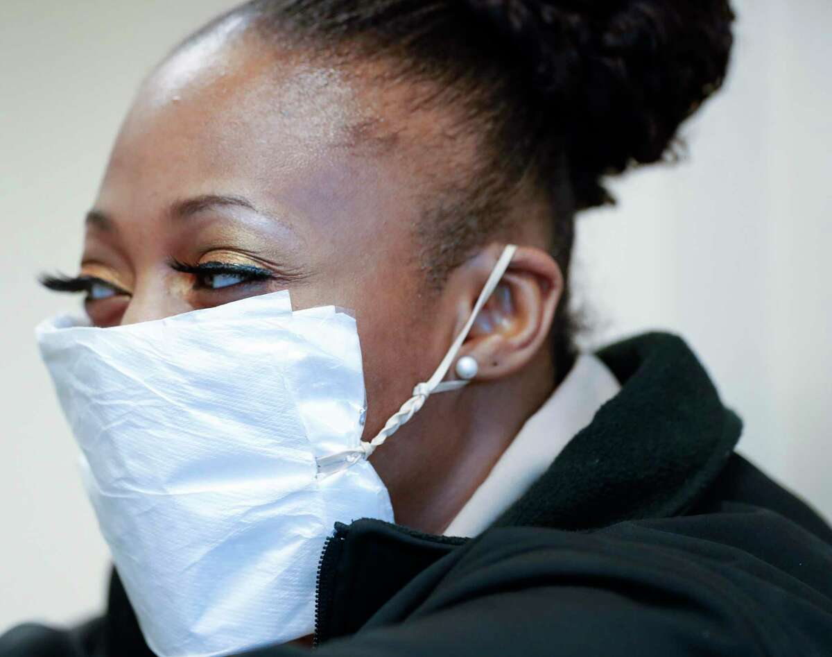 Security worker Shawna Butler wears a makeshift mask made from a napkin and a rubber band as she screens visitors before a Montgomery County Commissioners Court meeting at the Alan B. Sadler Commissioners Court Building, Tuesday. The county now has six confirmed cases.