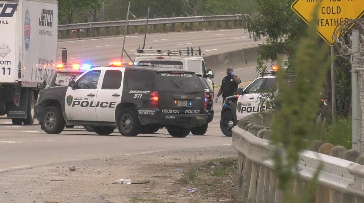 Houston police officers investigate the discovery of a body on the side of South Loop 610 near Calais on Wednesday, March 18, 2020.