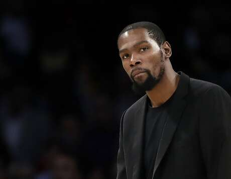 FILE- In this March 10, 2020, file photo, Brooklyn Nets' Kevin Durant watches during the second half of the team's NBA basketball game against the Los Angeles Lakers in Los Angeles. Durant is among the four Brooklyn Nets who have tested positive for the new coronavirus. (AP Photo/Marcio Jose Sanchez, file)