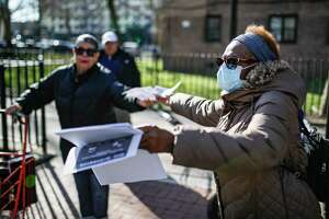 """A volunteer wearing protective gloves and face mask hands out informational fliers at City Harvest's Bed-Stuy Mobile Market operating in the Tomkins Houses area, Wednesday, March 18, 2020, in New York. Mayor Bill de Blasio said New York City residents should be prepared for the possibility of a """"shelter in place"""" order within days. De Blasio said Tuesday no decision had been made yet, but he wants city and state officials to make a decision within 48 hours given given the fast spread of the coronavirus."""