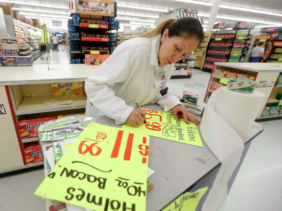 Elsa Avila creates signs for reduced prices for certain goods at Food Town, Wednesday, March 18, 2020, in New Caney. The grocery store established an elderly-only hour for shoppers 65-years or older from 7 a.m. to 8 a.m. Photo: Jason Fochtman, Houston Chronicle / Staff Photographer / Houston Chronicle  © 2020