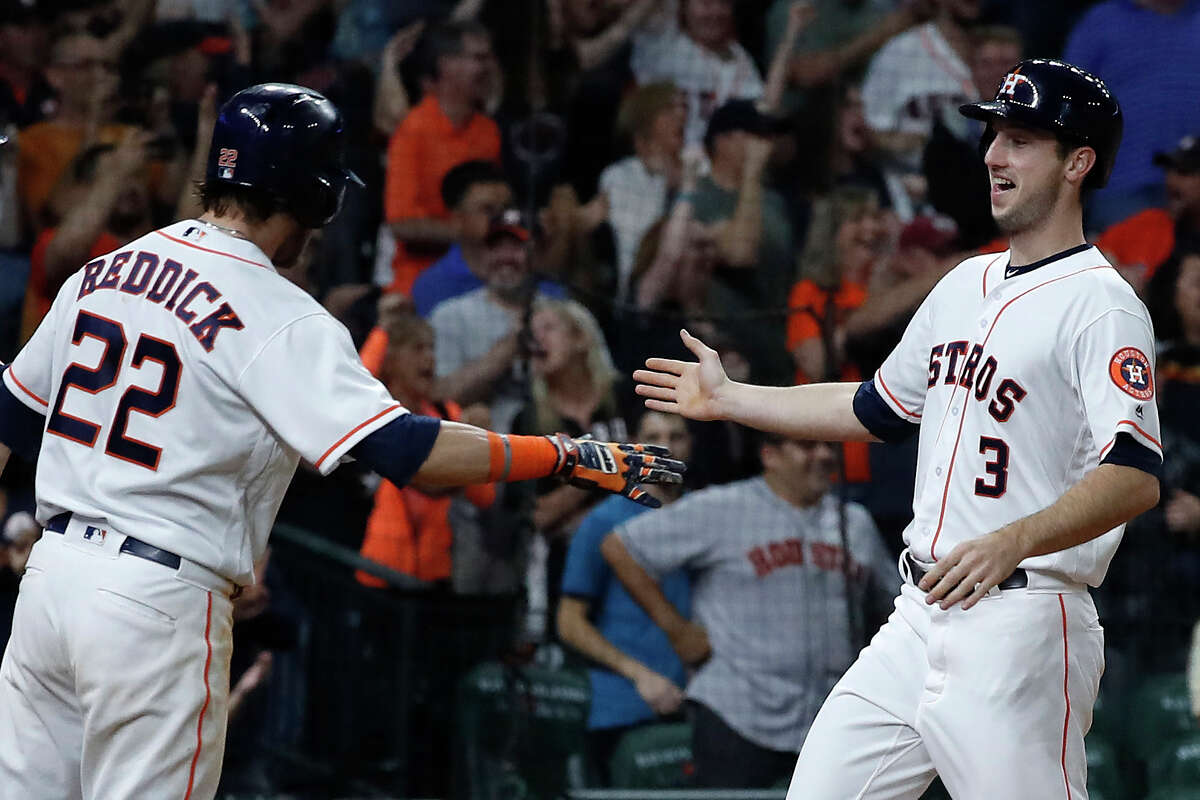 Kyle Tucker, congratulated by Josh Reddick after scoring a run last season, is tryiny to unseat the incumbent starting right fielder after spending part of last season with the Astros.
