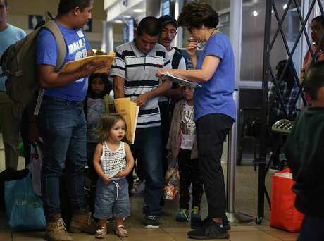 Juliet Giron, waits as her father, Brian Giron, 24, is helped by Interfaith Welcome Coalition volunteer Carolina Barrera at the Greyhound Bus station in San Antonio. They were kept together in family detention but later released as a family.