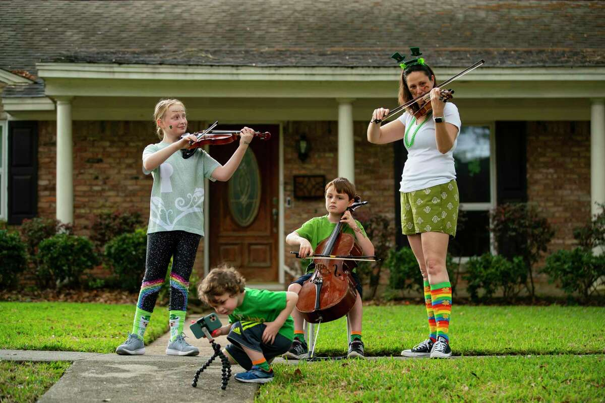 The Pichot family plays together in front of their home, Tuesday, March 17, 2020, in the Westbury neighborhood of Houston. Parker Elementary School Suzuki cello teacher Lisa Vosdoganes encouraged students at the HISD music magnet to take to their individual front yards at 10 am Tuesday morning to play together, apart.