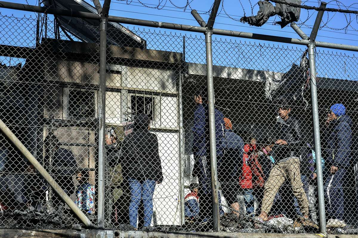 Migrants stand outside container houses in Moria refugee camp on the northeastern Aegean island of Lesbos, Greece, Monday, March 16, 2020. The Fire Service said a migrant, who was not further identified, was found dead inside Moria camp after the fire broke out Monday. (AP Photo/Panagiotis Balaskas)