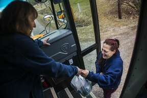Glenna Hall, left, passes bags filled with bagged lunches and breakfasts to Emily Beach, right, as bus drivers and volunteers deliver meals for Bullock Creek students Wednesday, March 18, 2020. (Katy Kildee/kkildee@mdn.net)
