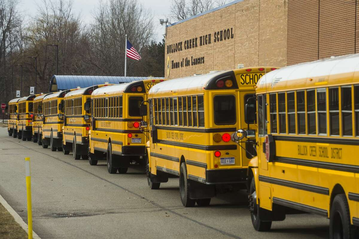 School buses line up to be stocked with breakfasts and lunches to be delivered to Bullock Creek students Wednesday, March 18, 2020. (Katy Kildee/kkildee@mdn.net)
