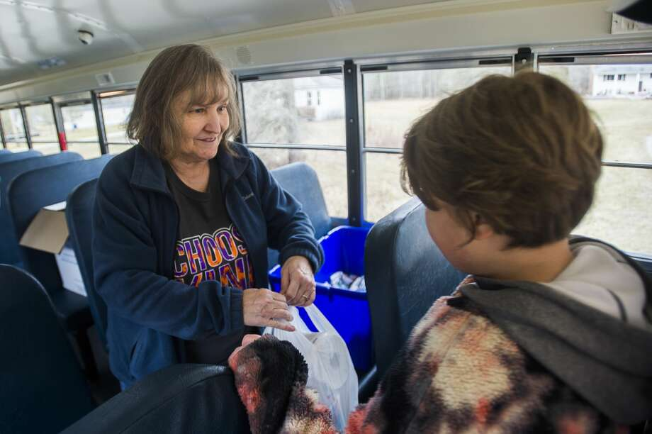 Glenna Hall, left, passes bags filled with bagged lunches and breakfasts to Phoenix Sinclair, 9, as bus drivers and volunteers deliver meals to Bullock Creek students Wednesday, March 18, 2020. (Katy Kildee/kkildee@mdn.net) Photo: (Katy Kildee/kkildee@mdn.net)
