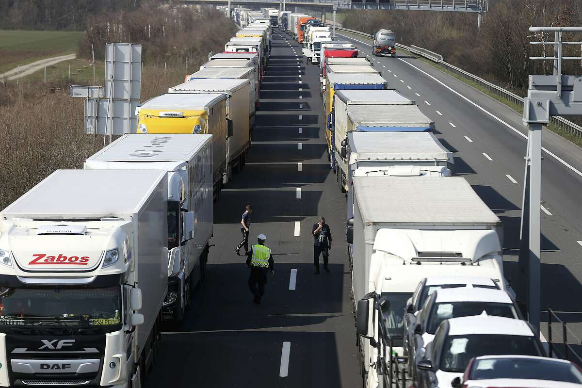Trucks stand on the highway close to the border between Austria and Hungary near Bruck an der Leitha, Austria, Wednesday, March 18, 2020. Hungary has closed the border due to the new coronavirus outbreak. Only for most people, the new coronavirus causes only mild or moderate symptoms, such as fever and cough. For some, especially older adults and people with existing health problems, it can cause more severe illness, including pneumonia. (AP Photo/Ronald Zak)