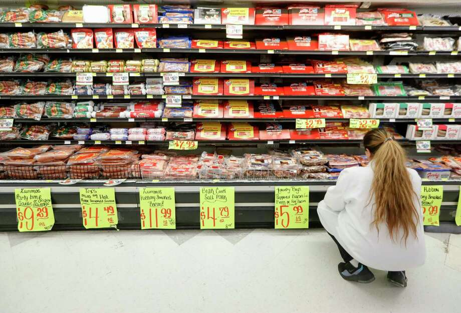 Elsa Avila hangs reduced prices signs for certain goods at Food Town, Wednesday, March 18, 2020, in New Caney. While there was a high demand as people in the area started to worry about staying isolated, it's important to remember that there isn't actually a food shortage. Photo: Jason Fochtman, Houston Chronicle / Staff Photographer / Houston Chronicle  © 2020