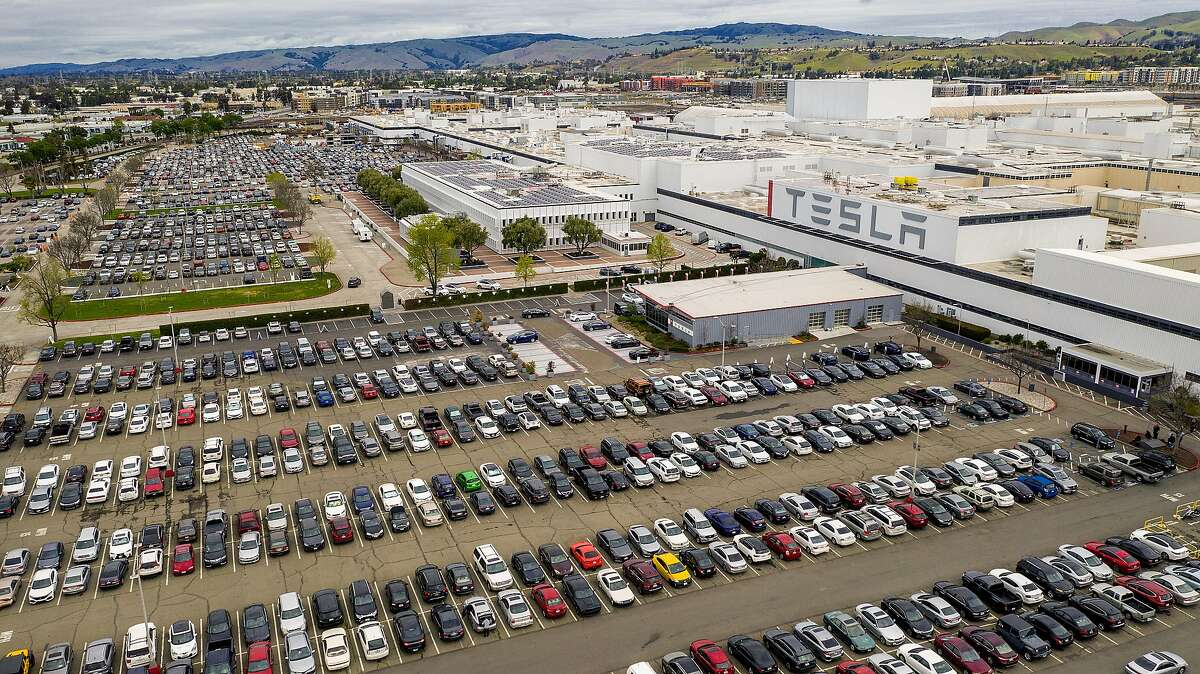 Cars line a parking lot at Tesla's Fremont, Calif., factory on Wednesday, March 18, 2020. The facility remains open despite Alameda County shelter-in-place orders to limit spread of the coronavirus.