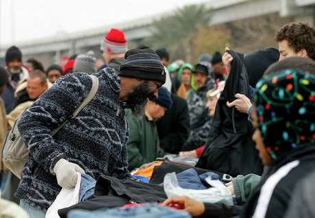 A homeless man looks through jackets and coats while going through the line during HOPE for Houston's day of outreach and donation drop off in downtown Houston near the Interstate 69 overpass Sunday, Jan. 12, 2020.
