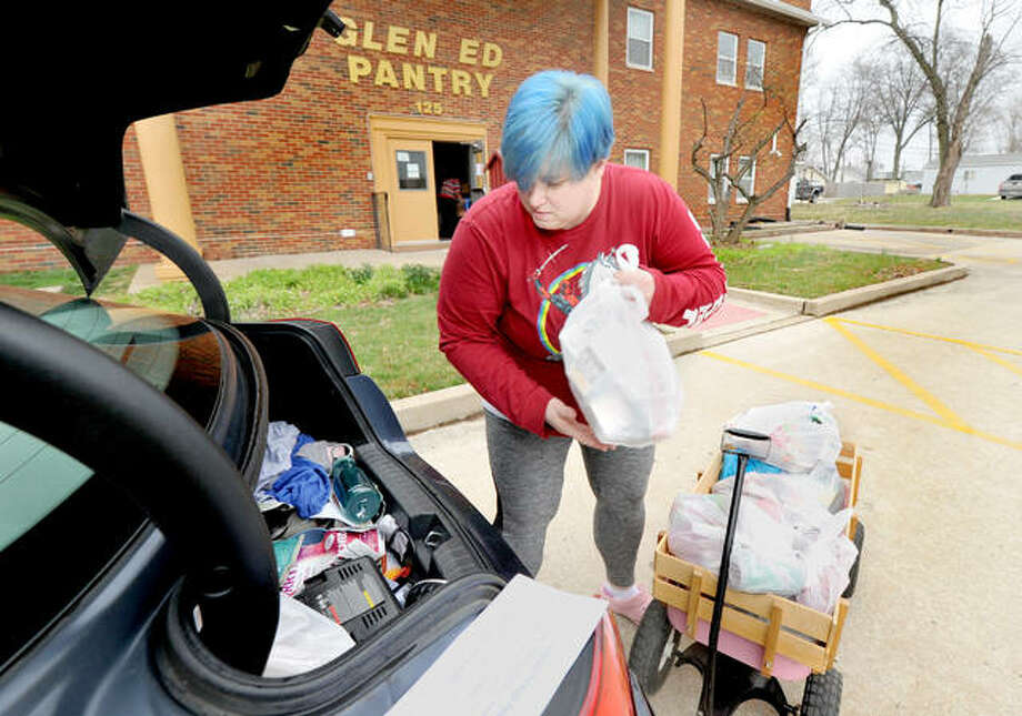 Jennifer Kilcrease of Edwardsville loads the trunk of her car with food from a wagon brought to her at the Glen-Ed Pantry Monday. Those getting food from the pantry had the food brought out to them instead of getting it inside the building as usual because of concerns from the coronavirus. Photo: Thomas Turney|For The Intelligencer