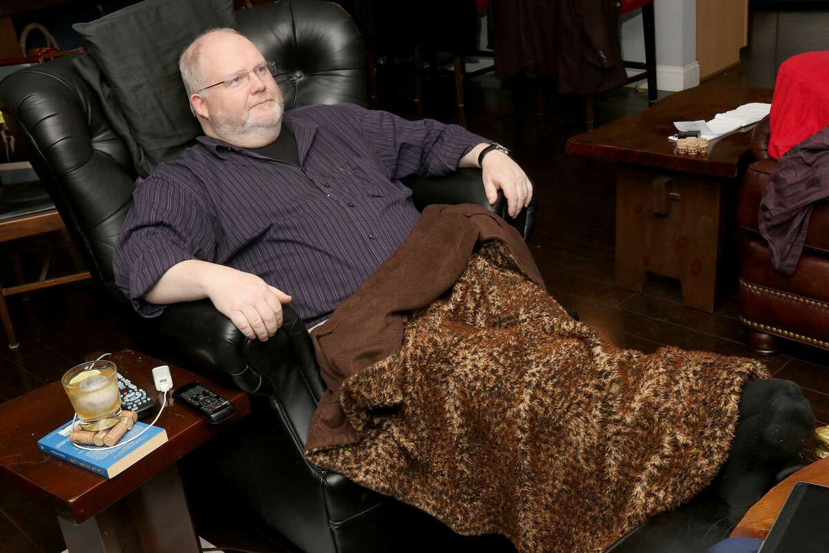 Restaurant critic and concert reviewer Steve Barnes takes advantage of an unexpected night off by staying home, catching up on some television and relaxing in his favorite chair with a blanket and a whiskey as all the shows he would have been reviewing were cancelled due to the Coronavirus. Albany, NY - March 14, 2020 - (Photo by Joe Putrock/Special to the Times Union) -