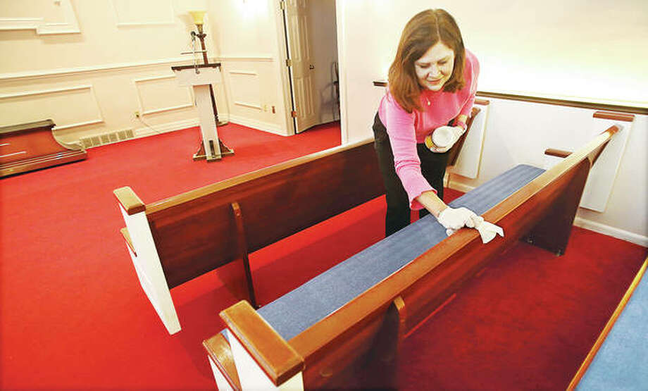 Laura Bosse', a secretary at Gent Funeral Home in North Alton, wipes down pews in the chapel at the mortuary this week. The funeral home is joining other public places in keeping surfaces that are frequently touched clean from the COVID-19 virus.