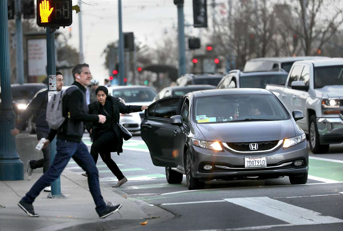 A passenger leaves a Lyft/Uber car on the Embarcadero at Mission St. as pedestrians cross the street on Wednesday, Jan. 29, 2020, in San Francisco, Calif.