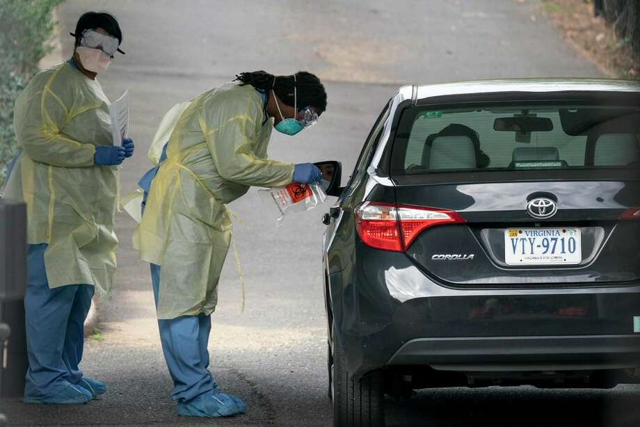 Health workers screen a patient for coronavirus on March 18 at a drive-through testing site in Arlington, Virginia. Photo: Drew Angerer/Getty Images