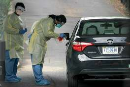 Health workers screen a patient for coronavirus on March 18 at a drive-through testing site in Arlington, Virginia.