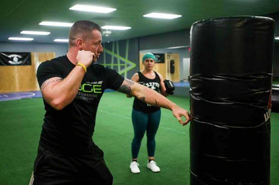 Brian Patrick, owner of Edge Fitness and Training Headquarters, gives insruction to Amanda Austin of Essexville, right, and Adrienne Gibson of Hope (not pictured) during a kickboxing class at the gym in Midland. (Katy Kildee/kkildee@mdn.net)
