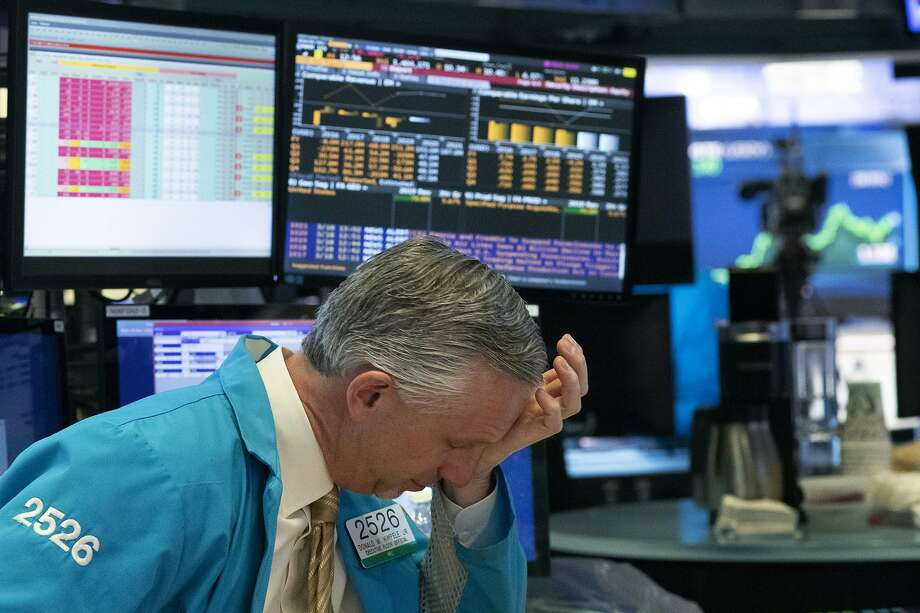 A trader holds his hand to his head after trading was halted at the New York Stock Exchange, Wednesday, March 18, 2020,  in New York. (AP Photo/Mark Lennihan) Photo: Mark Lennihan / Associated Press