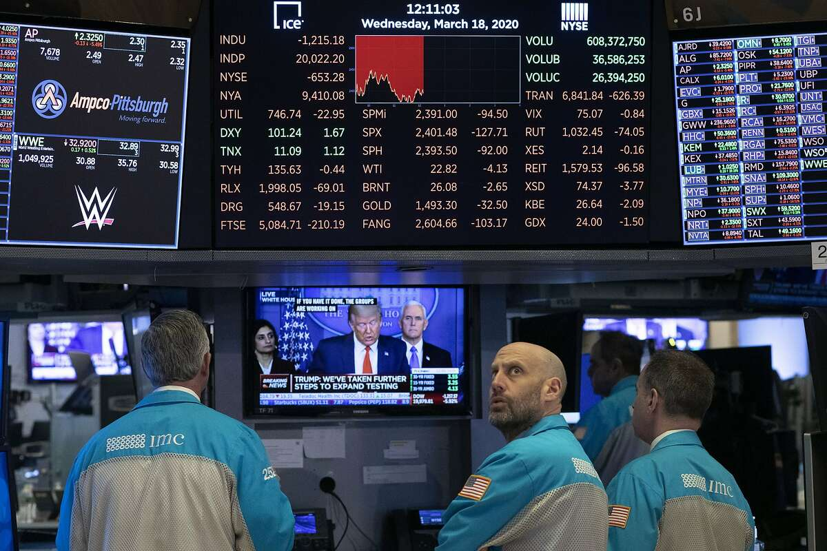 Traders at the New York Stock Exchange watch President Donald Trump's televised White House news conference, Wednesday, March 18, 2020 in New York. (AP Photo/Mark Lennihan)