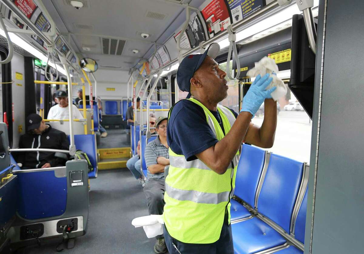 Rodney Norman wipes down a VIA bus at a stop at Centro Plaza transfer station last March as coronavirus precautions began.