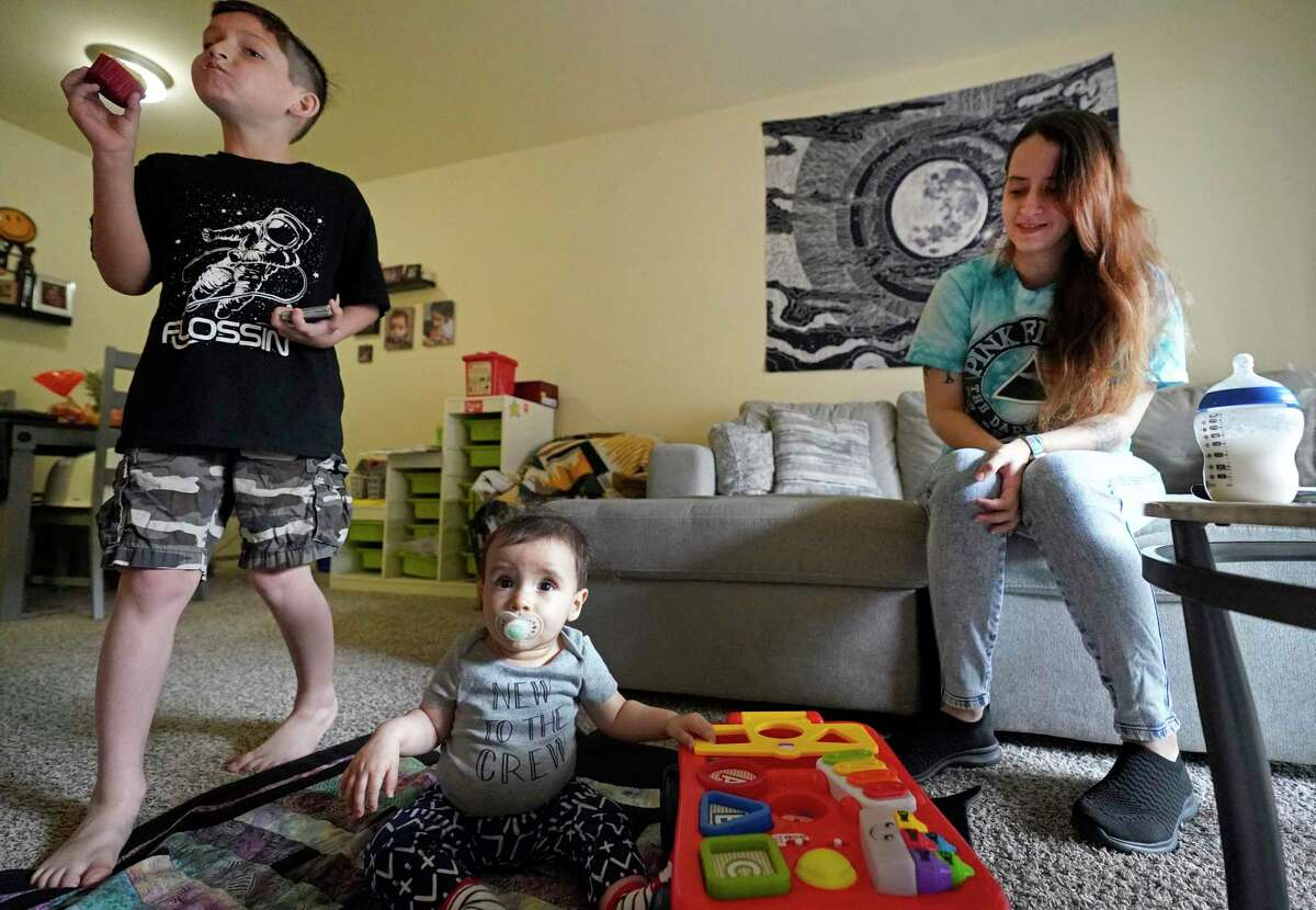 Ruthy Raske with her sons, J.P., 7, and 8-month-old, Santi, in their Memorial area apartment Wednesday, March 18, 2020, in Houston. She is a server at a restaurant that just had to close its dining room for two weeks. She's about to move into a larger unit at her complex and is worried about her job and paying rent.