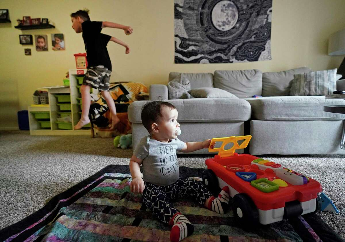 J.P. Raske, 7, plays in the living room along with his 8-month-old brother, Santi, as their mom, Ruthy Raske, prepares lunch in their Memorial area apartment Wednesday, March 18, 2020, in Houston. She is a server at a restaurant that just had to close its dining room for two weeks. She's about to move into a larger unit at her complex and is worried about her job and paying rent.