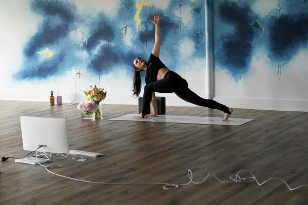 Sarah Gordon leads a livestream yoga class at Atrium Yoga Studio, 3733 Westheimer, Wednesday, March 18, 2020, in Houston. Atrium Yoga closed its studio down on Saturday, a few days after WHO declared it a pandemic. They started offering livestream yoga classes on Monday.