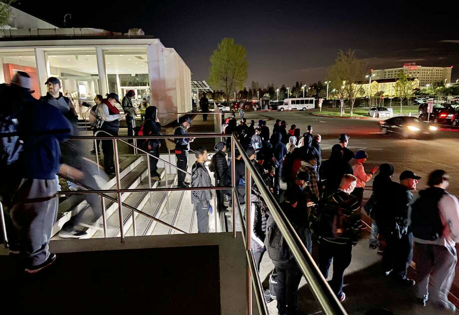 Tesla workers coming off the night shift workers wait to board busses at the Fremont factory. Photo: Russ Mitchell/TNS