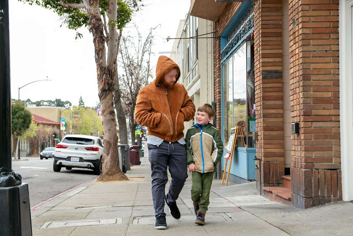 Jack Tone-Riordan, 39, and son River, 6, take a walk to get fresh air on the second day of sheltering in place orders on March 18, 2020 in Oakland, Calif.