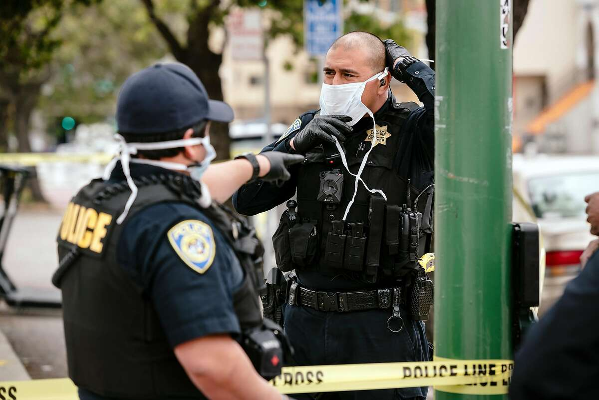 BART police officers put on face masks as they prepare to investigate a deceased male outside the Lake Merritt BART station in Oakland, California, US, on Wednesday, March 18, 2020.