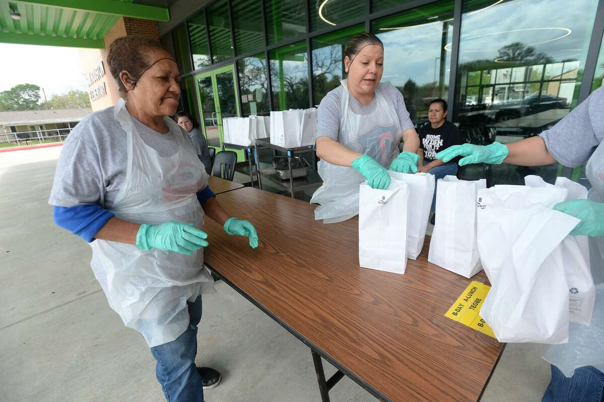 Lillian Ward and Maregarita Figuero help with the assembly line of sack lunches for distribution at Sam Houston Elementary on the first day of breakfast and lunch distribution for Port Arthur ISD students, as well as any children 18 and under who arrive to get a meal. Photo taken Wednesday, March 18, 2020 Kim Brent/The Enterprise